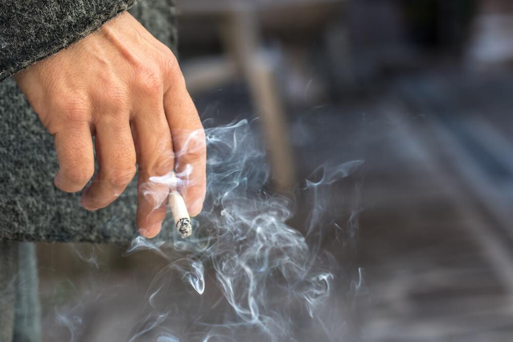 Person Holding Lit Cigarette