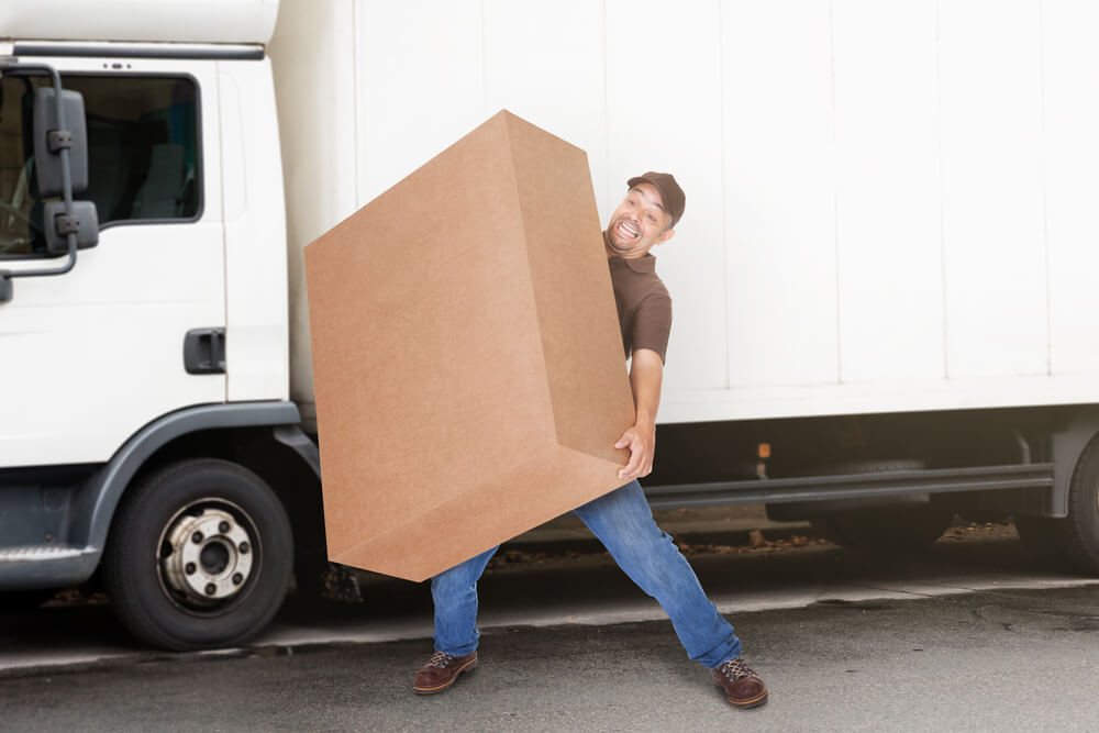 Man Struggling to Carry Heavy Box