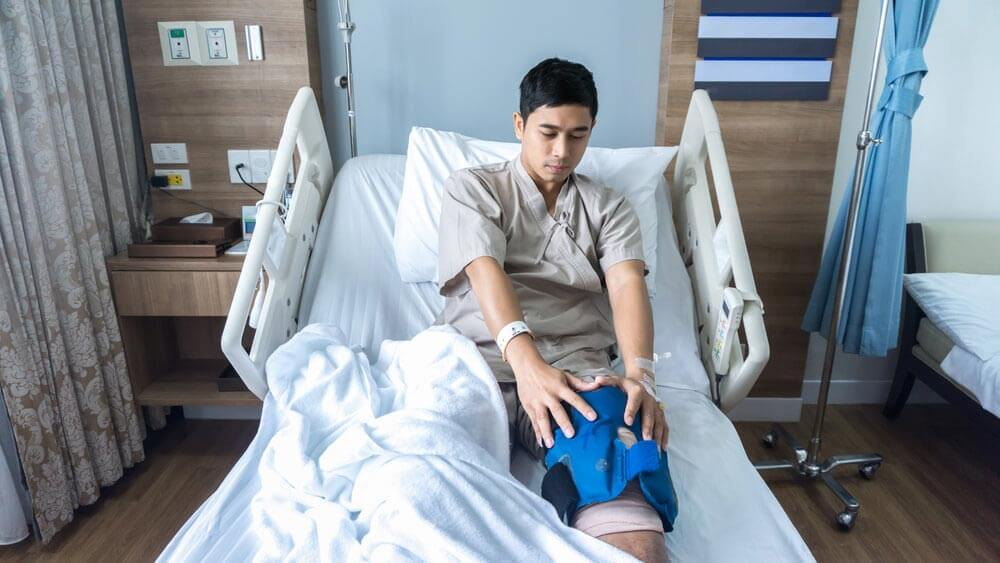 Knee Operation Patient in Hospital Holding His Knee