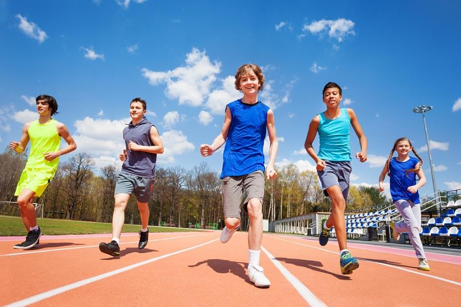 Teenagers Running Around Athletics Track