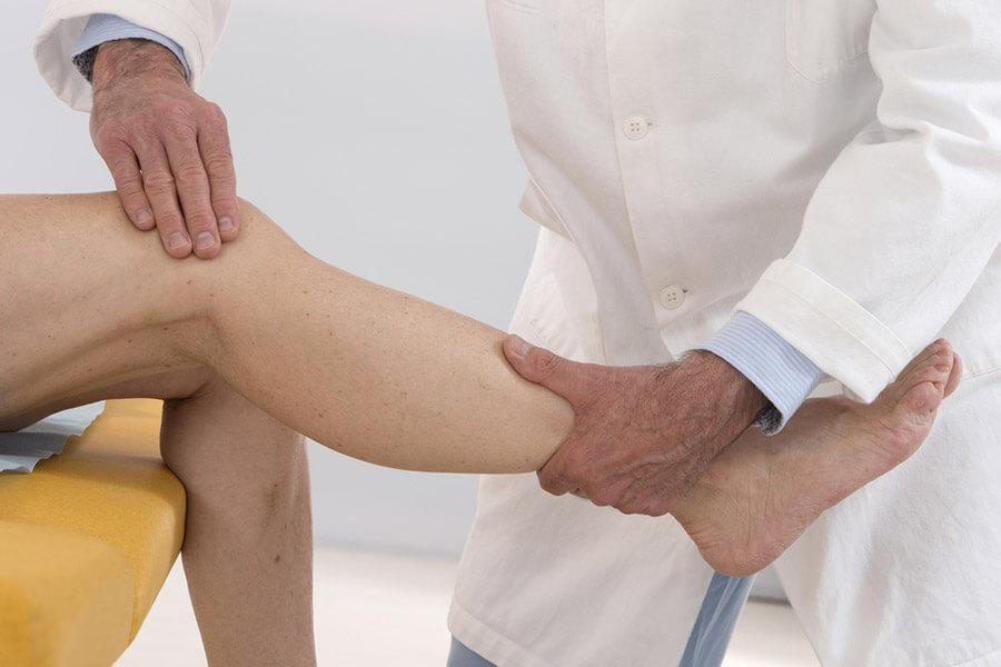 Consultant examining patients knee