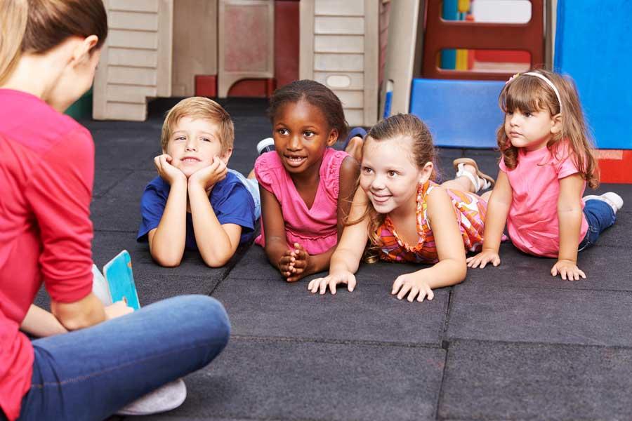 Nursery Nurse sitting down on floor talking with children