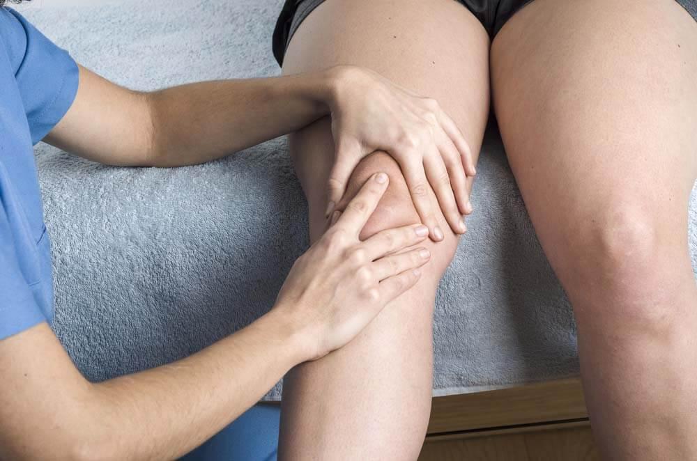 Nurse Examining Patient's Kneecap